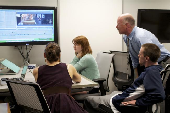 Students and professor editing a video together.