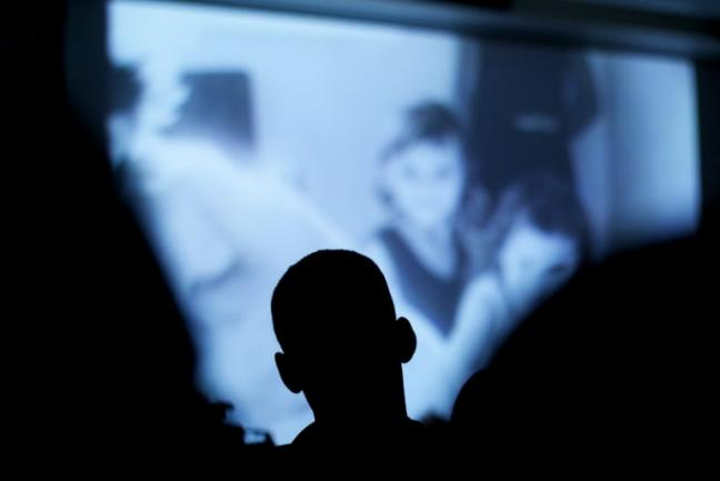 Silhouette of a student in front of a movie screen/